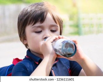 Cute little boy drinking colding from clear glass bottle in the hot sunny day on summer, Kid boy drink soda or soft drink sitting in street with blurry background