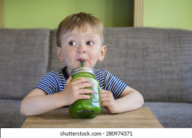 Cute little boy drinking a green smoothie