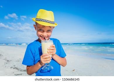 Cute little boy drinking juice on tropical summer beach