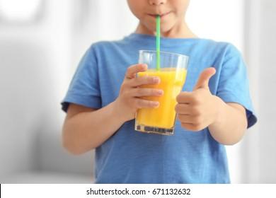 Cute little boy drinking juice at home, closeup