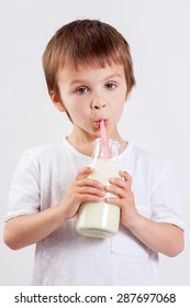Cute little boy, drinking milk, holding glass of milk, mustaches from the milk, smiling at camera, isolated on white