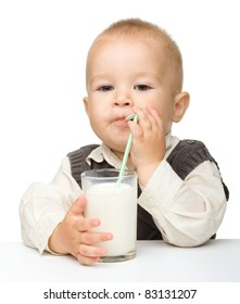 Cute little boy is drinking milk using drinking straw while sitting at table, isolated over white