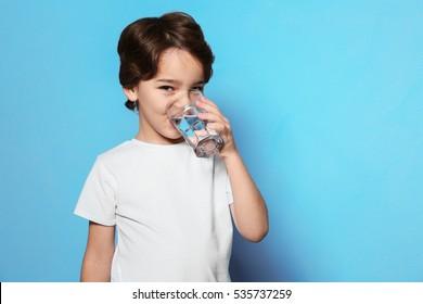 Cute little boy drinking water from glass on blue background - Shutterstock ID 535737259