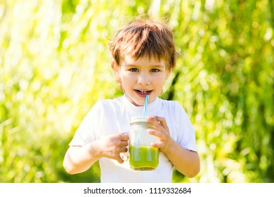 Cute little boy drinks healthy green smoothie with straw in a jar mug against the background of greenery outdoor.