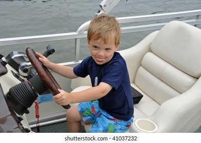 a cute little boy drives a boat while sticking out his tongue