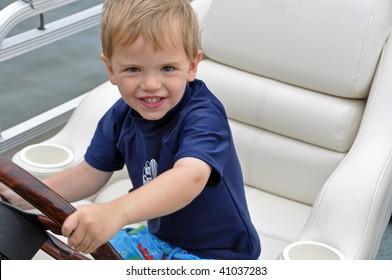 a cute little boy drives a boat