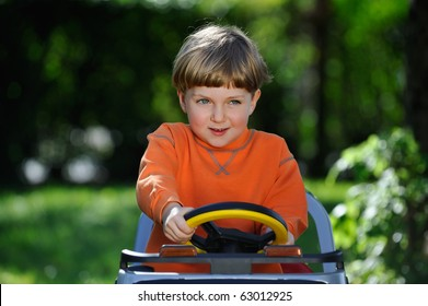 cute little boy driving an electric car