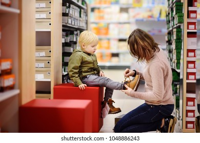 Cute little boy during shopping with his young mother. Kid trying new fashion seasonal shoes. Child in shopping center/mall or baby apparel store.