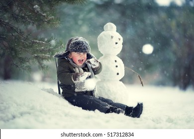 Cute little boy in earflaps hat sitting near a snowman and being thrown a snowballs. Image with selective focus and toning