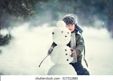 Cute little boy in earflaps hat with a snowman. Image with selective focus and toning