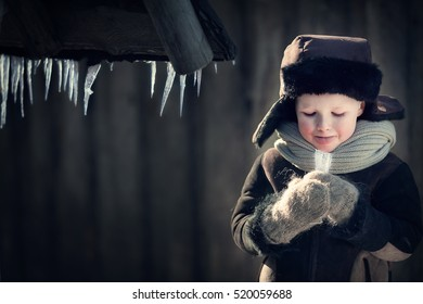 Cute little boy in earflaps hat is licking an icicle in winter in the country in Russia. Image with selective focus and toning