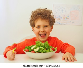Cute little boy eating bowl with salad