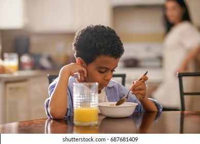 cute little boy eating breakfast with mother behind him in kitchen