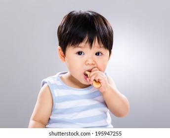 Cute little boy eating cookie