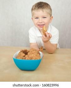 Cute little boy eating cookies