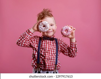 Cute little boy is eating donut on pink background. child is having fun with donut. Tasty food for kids. Funny time at home with sweet food. Bright and stylish kid.