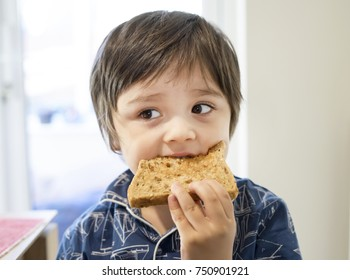 Cute little boy eating honey on toasted for his breakfast, Healthy children or Healthy food for kid concept