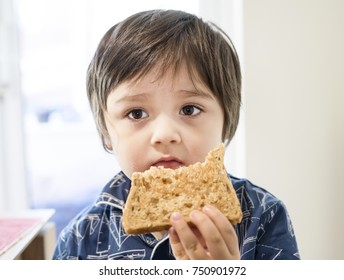 Cute little boy eating honey on toast for his breakfast, Healthy children or Healthy food for kid concept