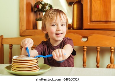 Cute little boy eating a stack of pancakes in kitchen.