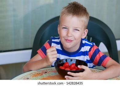 Cute little boy eating a strawberry