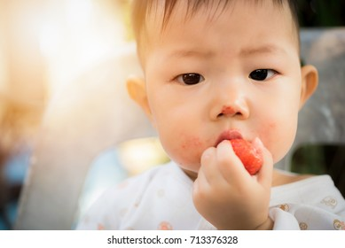 Cute little boy eats strawberries, asia baby eating strawberry on chair outdoor