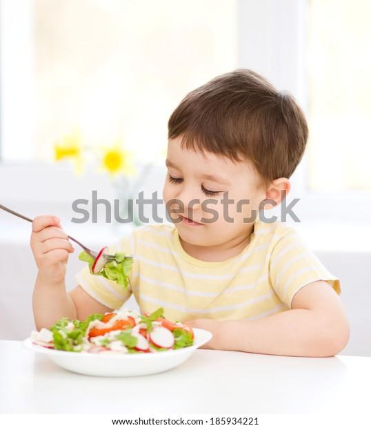 Cute little boy eats vegetable salad using fork