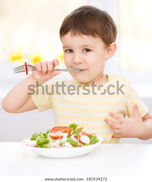 Cute little boy eats vegetable salad using fork
