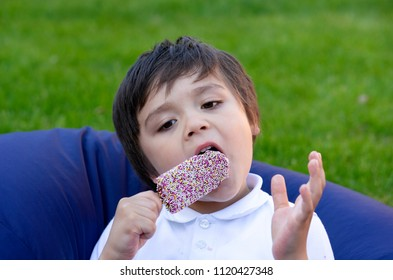 Cute little boy enjoy eating and ice cream lollipop covered colored sprinkles, Kid sitting in bean bag in the garden eating an ice cream for his snack after back from school