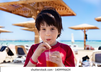 Cute little boy enjoying apple juce during tropical vacation at the seaside. Adorable child drinks tasty coctail from a straw with pleasure in a hot day at the beach.