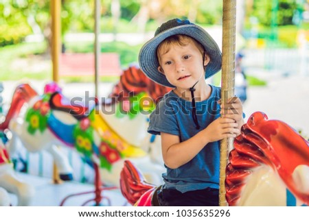 f84f0b8a5 Cute little boy enjoying in funfair and riding on colorful carousel house
