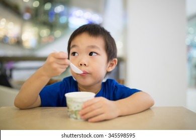 Cute little boy enjoying ice cream in cafe.