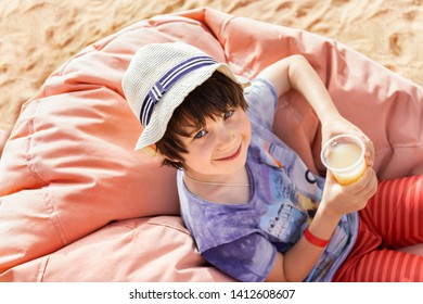 Cute little boy enjoying juce during tropical vacation at the seaside. Adorable child drinks tasty coctail  with pleasure sitting in a cosy bean bag chair in a hot day on the beach.