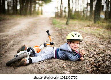 Cute little boy fallen off his bicycle outdoors, but he's feel ok, don't cry, even smile, he's all good. Concept of sport and safety, kids ride bicycle; first bike; active toddler kid playing