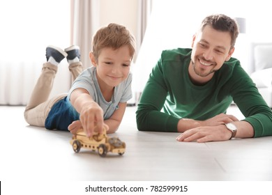 Cute little boy and father playing with toy car on floor at home