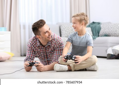 Cute little boy with father playing videogame at home