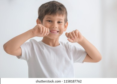 Cute little boy flossing his teeth on light background
