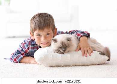 Cute little boy with fluffy cat lying on floor at home