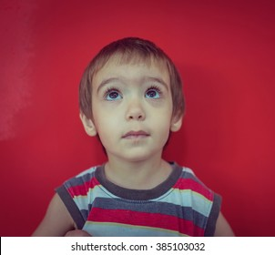 Cute little boy in front of red wall