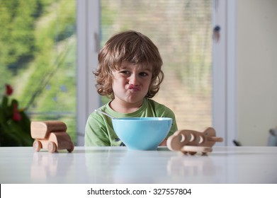 Cute little boy frowning over his meal while playing with toys. Bad behavior,  eating habbits concept