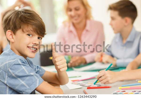 Cute little boy gesturing thumb up by fingers during drawing lesson. Positive male pupil wearing blue shirt smiling and looking at camera sitting with classmates and teacher on blurry background.