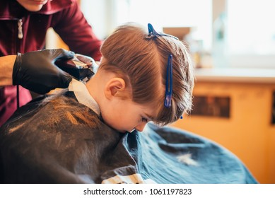 Cute little boy is getting haircut by hairdresser at the barbershop