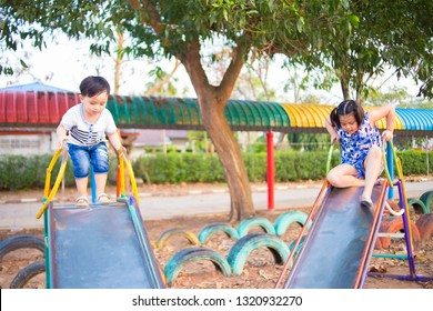 Cute little boy and girl having fun on kids riding from children slides in beautiful summer garden on warm and sunny day outdoors. Active summer playing for kids.