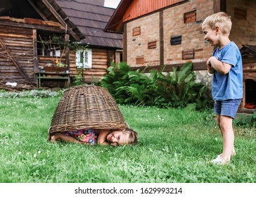 Cute little boy and girl having fun together and playing with hurdled basket on the backyard of old country house in village at summer, happy summertime in countryside, outside emotional lifestyle