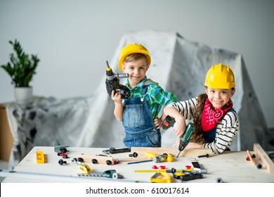 Cute little boy and girl playing with toy tools and smiling at camera