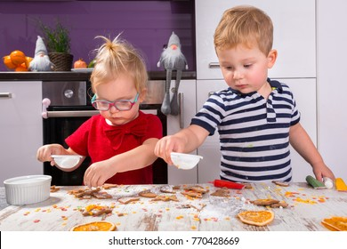 Cute little boy and girl twins decorating Christmas cookies in the kitchen