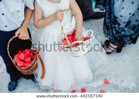 21e83f85dd895 Cute little boy and girl in a white dress and suit with basket throwing red  rose
