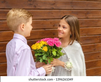 Cute little boy giving bouquet of flowers to charming little lady – smiling girl in love receiving yellow and pink roses from friend – generation z friendship concept with two happy kids outdoor