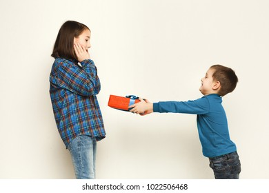 Cute little boy giving his sister gift, white studio background. Birthday celebration, brother congratulating his sis, copy space.