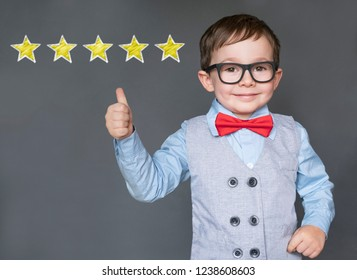 Cute little boy giving thumbs up with 5 stars approved