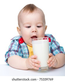 Cute little boy is going to drink milk from big glass while sitting at table, isolated over white